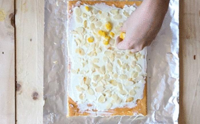 Rắc hạnh nhân rang đều lên mặt bánh vừa được phết kem