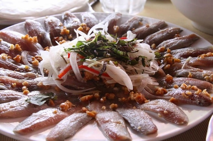 Ăn gỏi cá trích kèm với bún tươi, cuộn với bánh tráng cuốn và các loại rau thơm